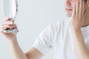 鏡を見て肌を確認する男